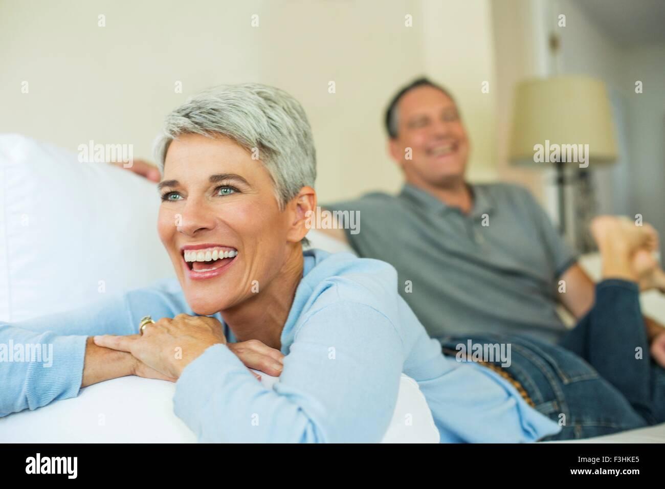 D'âge mûr de rire et de détente sur canapé Photo Stock