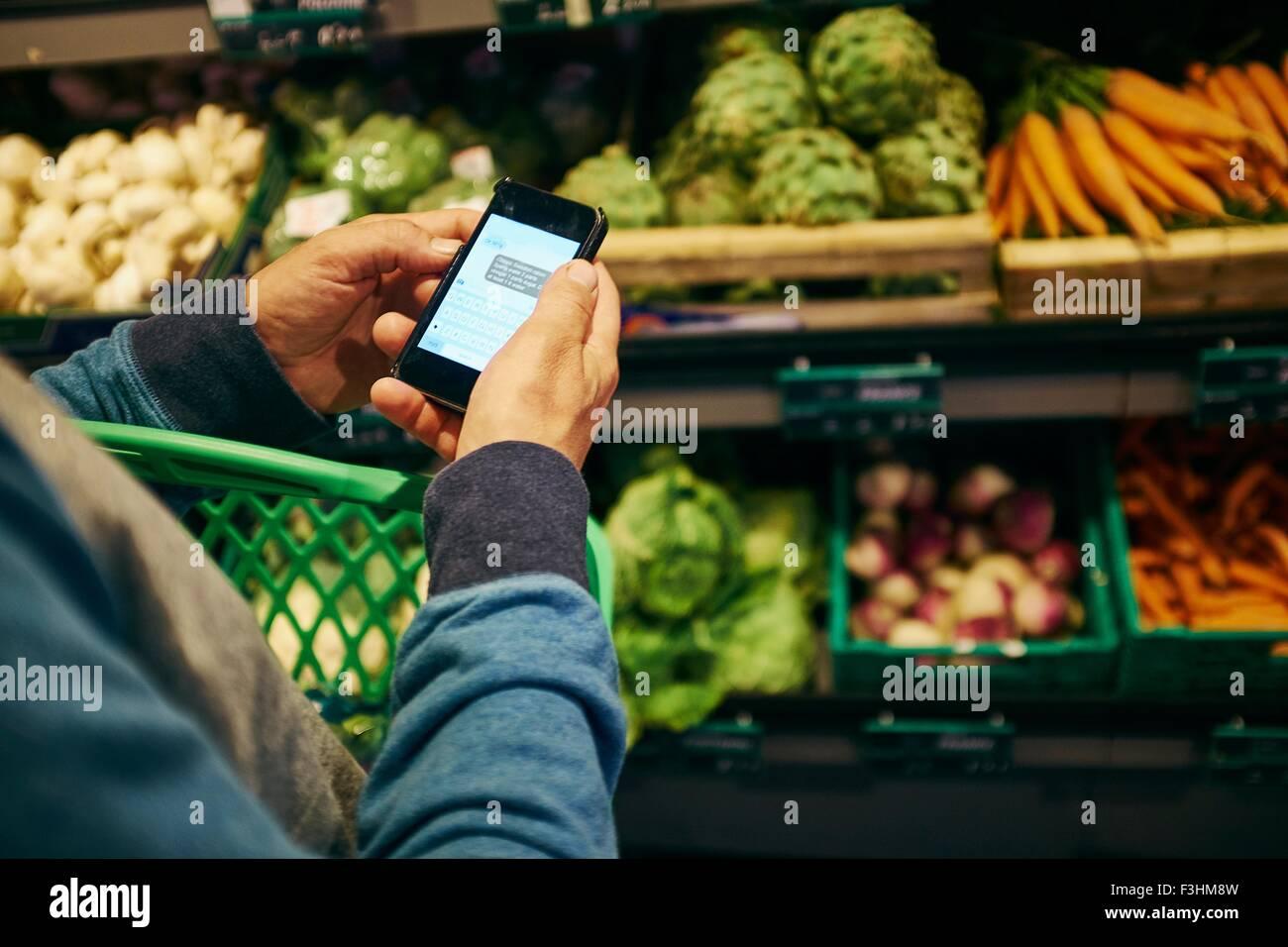 Man shopping et l'utilisation de smartphone dans un supermarché Photo Stock