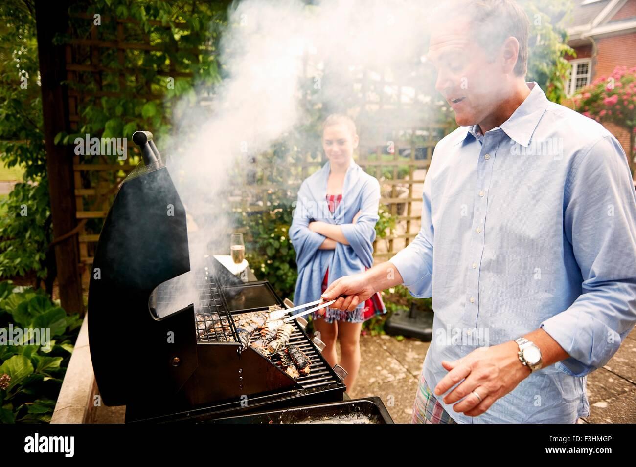 Fille regardant père cook sea food sur barbecue Photo Stock