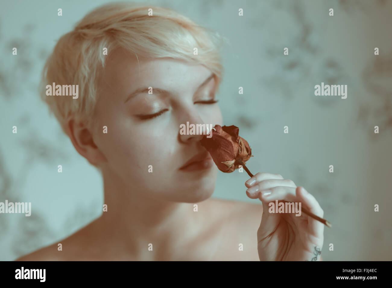 Blonde teenage girl holding a dead rose Banque D'Images