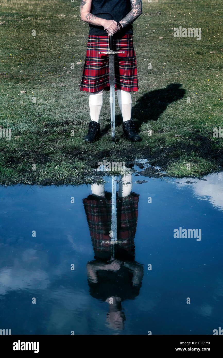 Un écossais avec son épée, voyant dans le reflet d'un étang Photo Stock