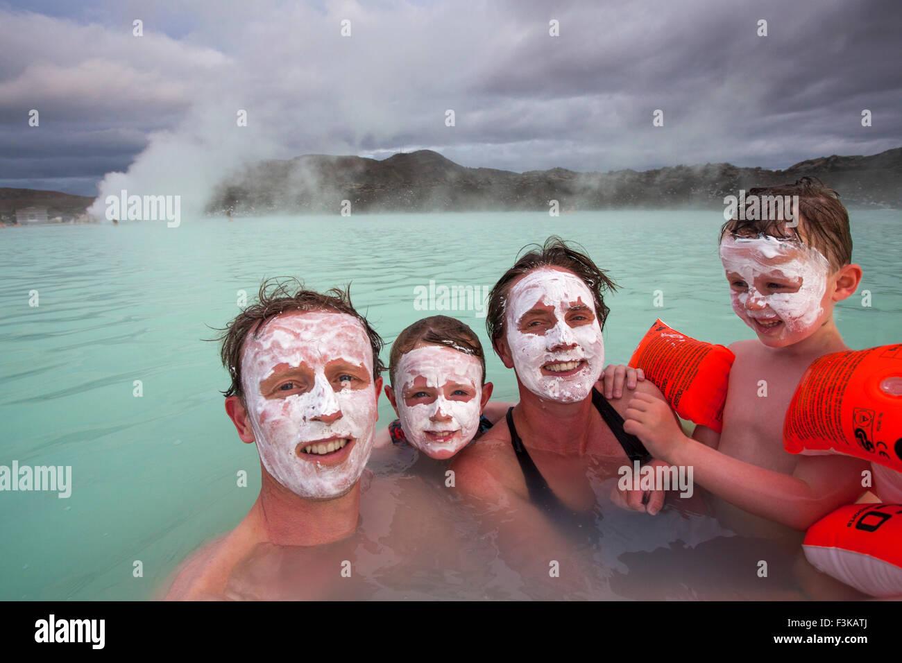 Famille avec de la boue de silice masque de visage swimmning au spa géothermal Blue Lagoon. Grindavik, Islande. Banque D'Images