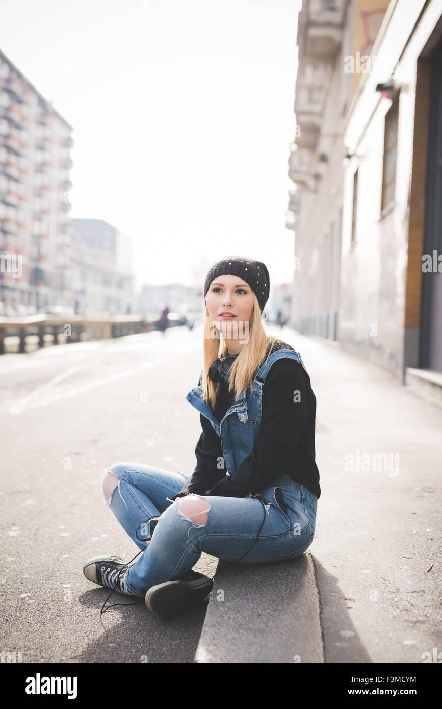Jeune belle blonde les cheveux droits femme dans la ville, assis sur le sol, donnant sur la droite, tenant un smartphone, Photo Stock