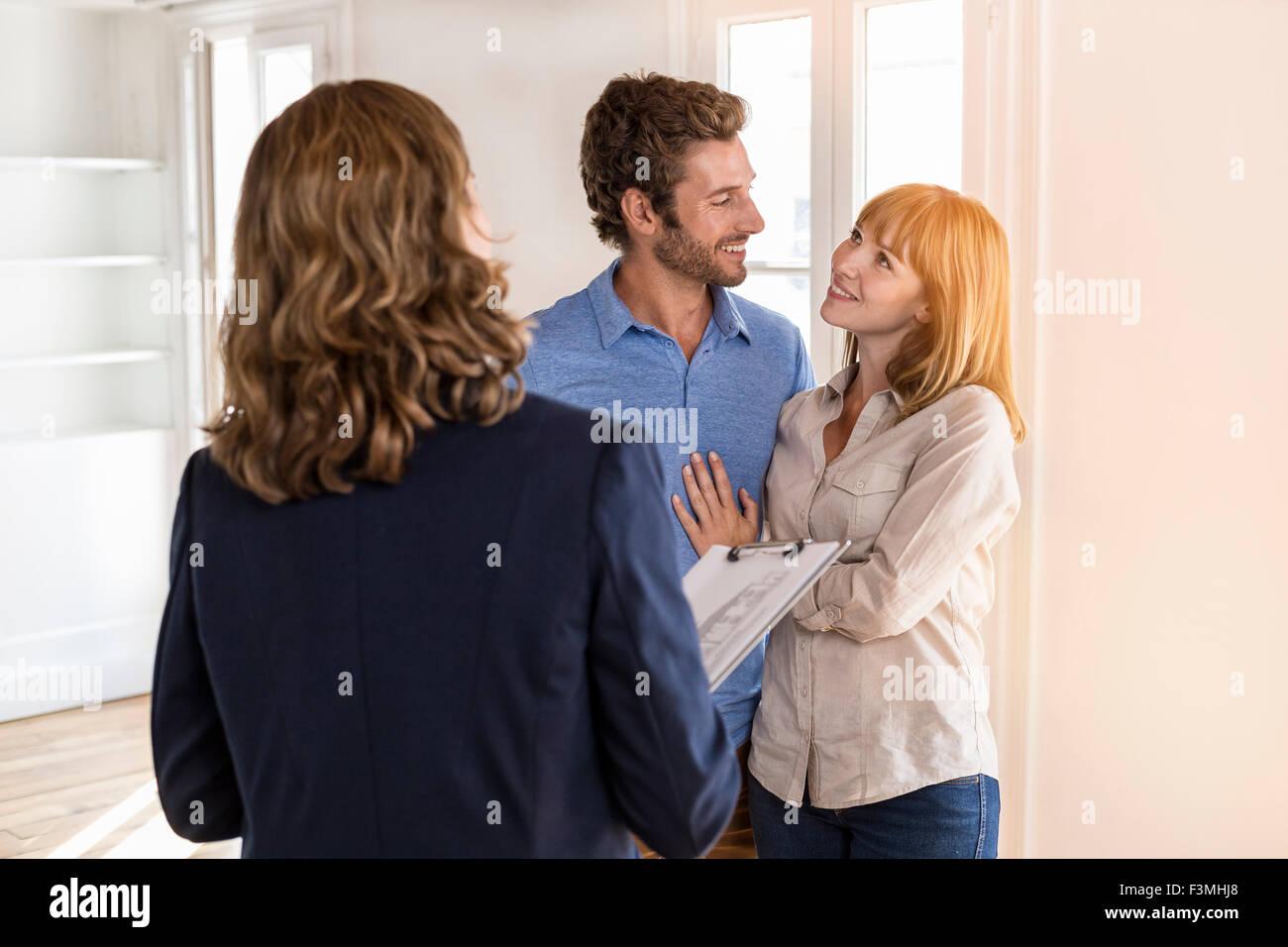 Agent immobilier appartement blanc moderne montrant aux futurs propriétaires couple Photo Stock