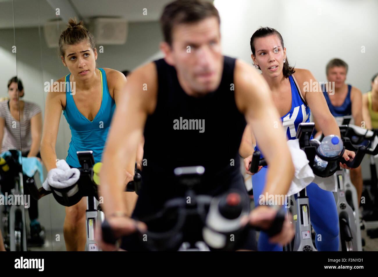 Les jeunes femmes équitation vélo stationnaire pendant un cours de gym spinning Photo Stock