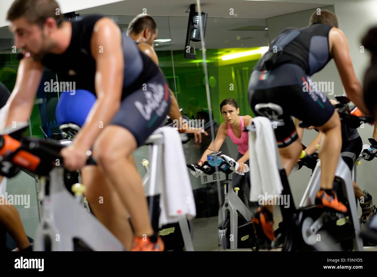 Jeune femme équitation vélo stationnaire pendant un cours de gym spinning Photo Stock