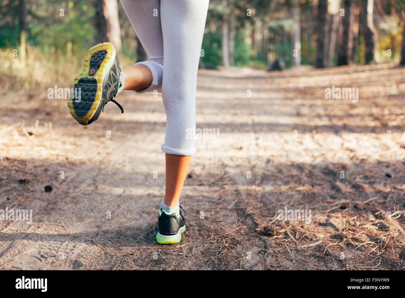 Pieds d'exécution sur Road Runner close-up sur Chaussure femme au lever du soleil remise en forme. Photo Stock