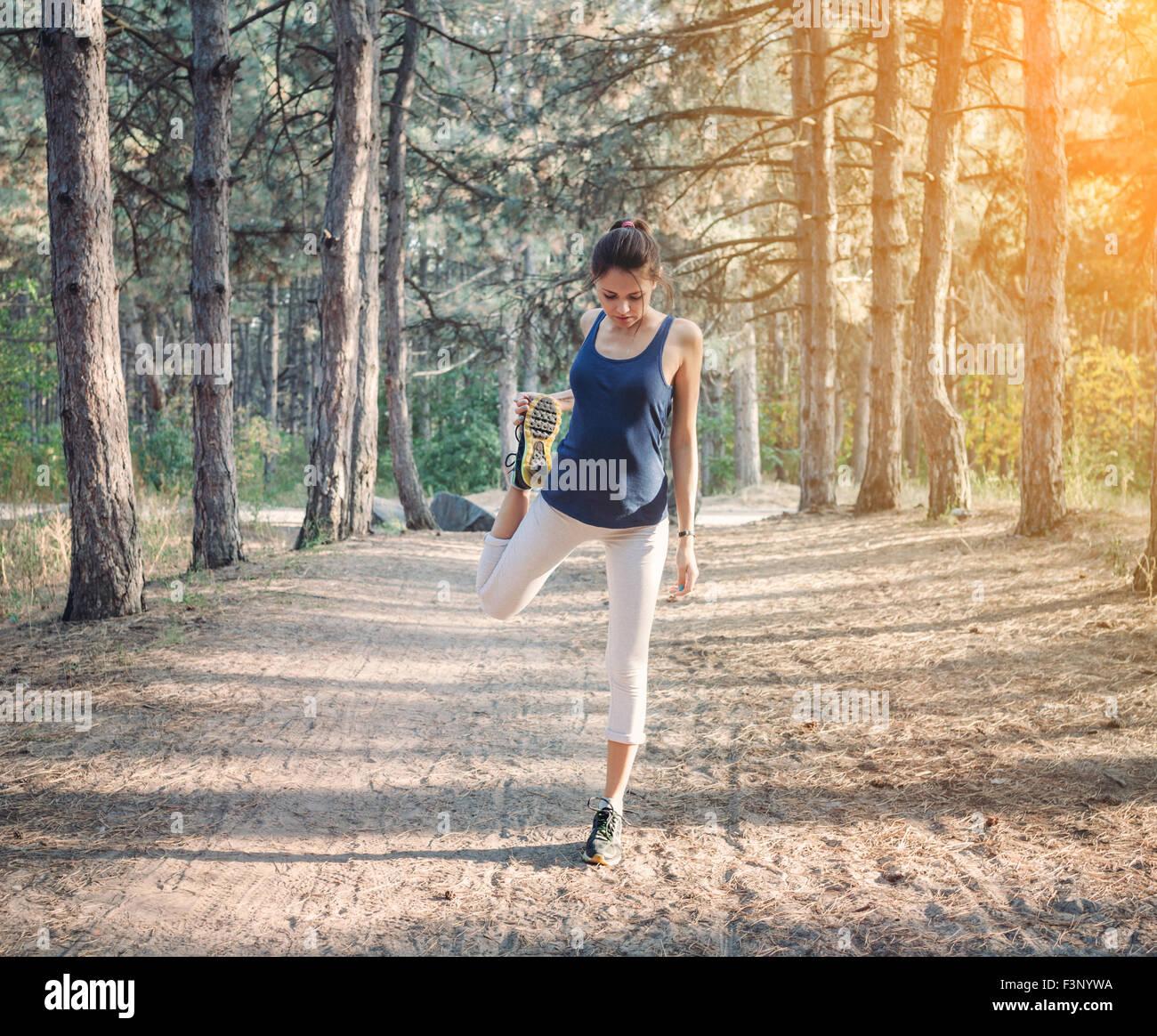 Jeune fille belle sports dans la forêt d'automne au coucher du soleil Photo Stock