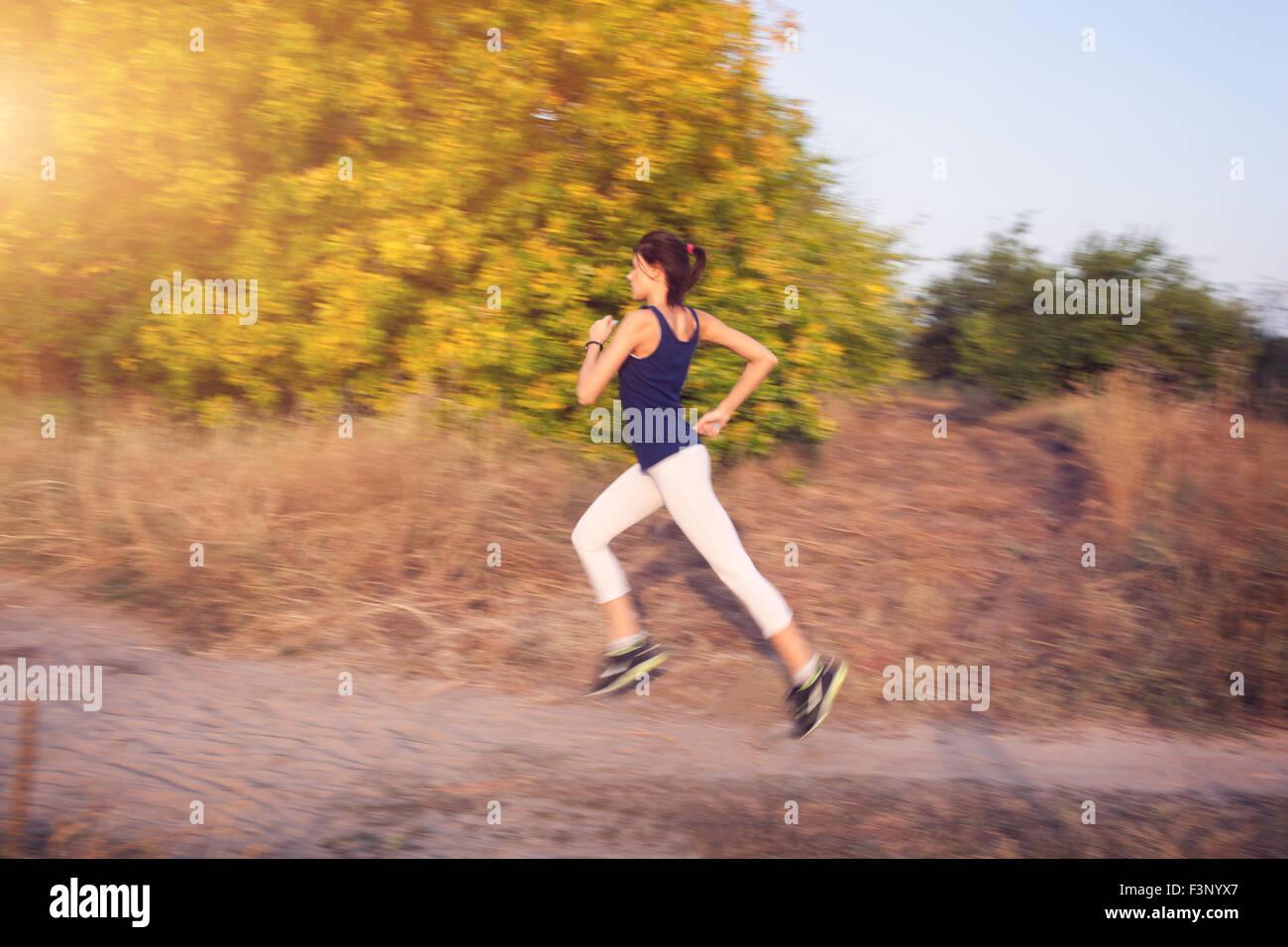 Jeune femme tournant sur un chemin rural au coucher du soleil dans la forêt d'automne. Fond sports Lifestyle Photo Stock