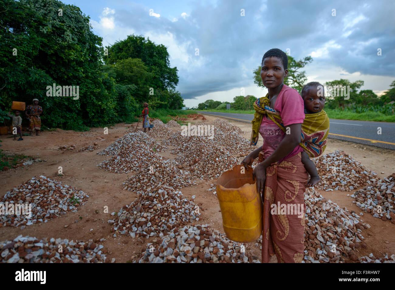 Femme avec bébé recueille des pierres, le Mozambique, l'Afrique Photo Stock