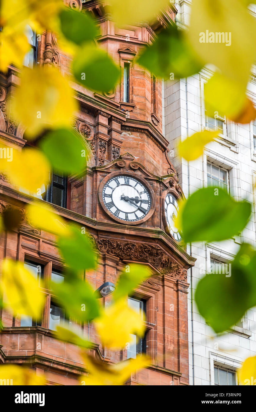 Une horloge à travers les feuilles de couleur automnale, Glasgow, Écosse, Royaume-Uni Banque D'Images