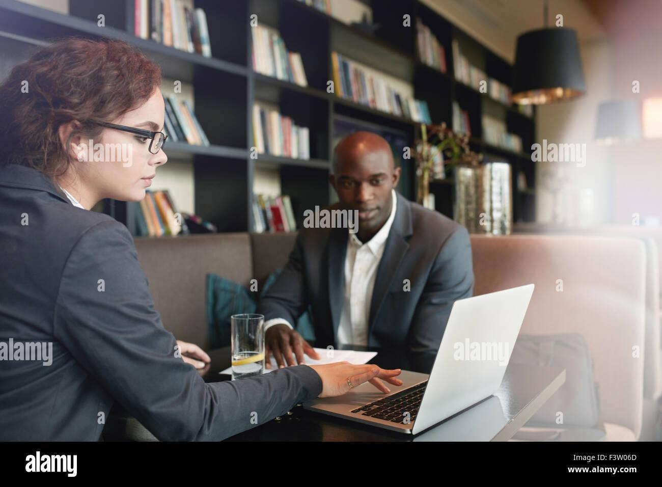 Young businesswoman working on laptop avec son partenaire en affaires tout en étant assis au café. De Photo Stock