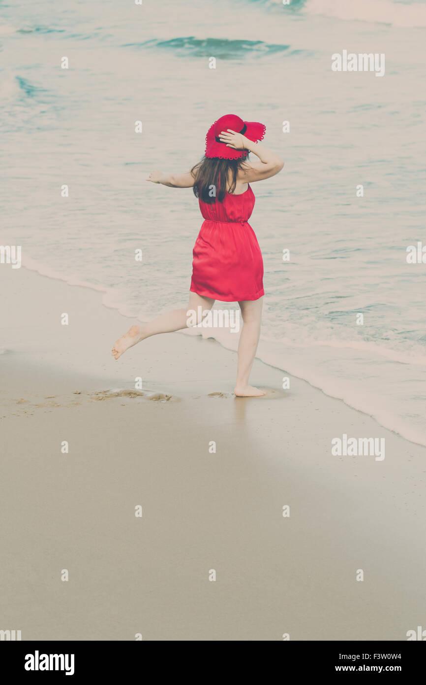 Jeune femme en robe rouge sur la plage Photo Stock