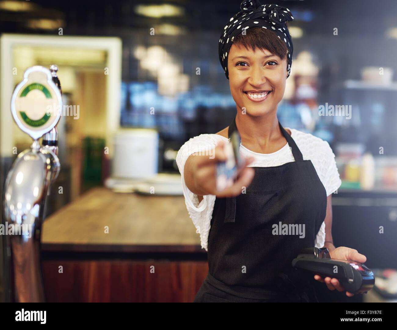 Belle vivacité young African American bar offre la restitution d'une carte bancaire après paiement Photo Stock