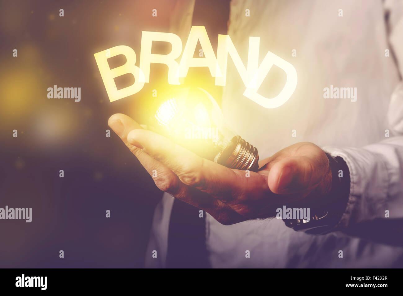 Idée de marque concept avec businessman holding ampoule, tons rétro droit, selective focus. Banque D'Images