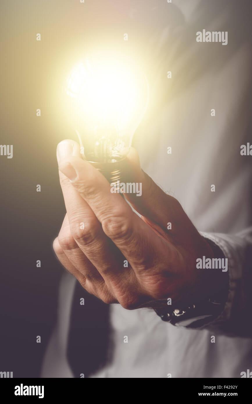 Mettre en place les nouvelles idées d'entreprise, homme d'affaires avec ampoule électrique offrant Photo Stock