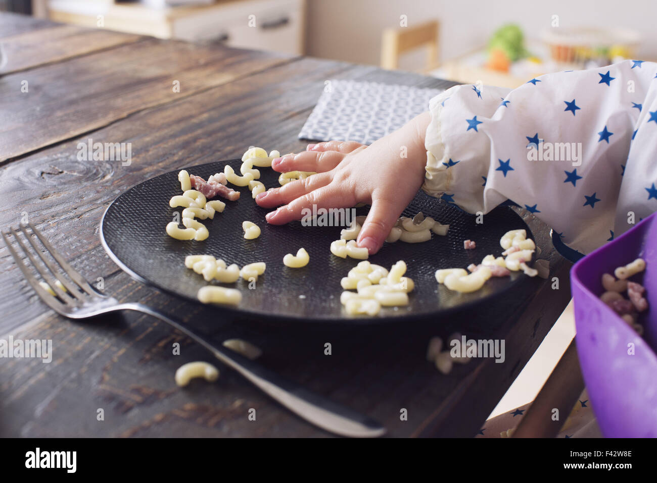 Enfant de manger des macaronis avec sa main, cropped Photo Stock