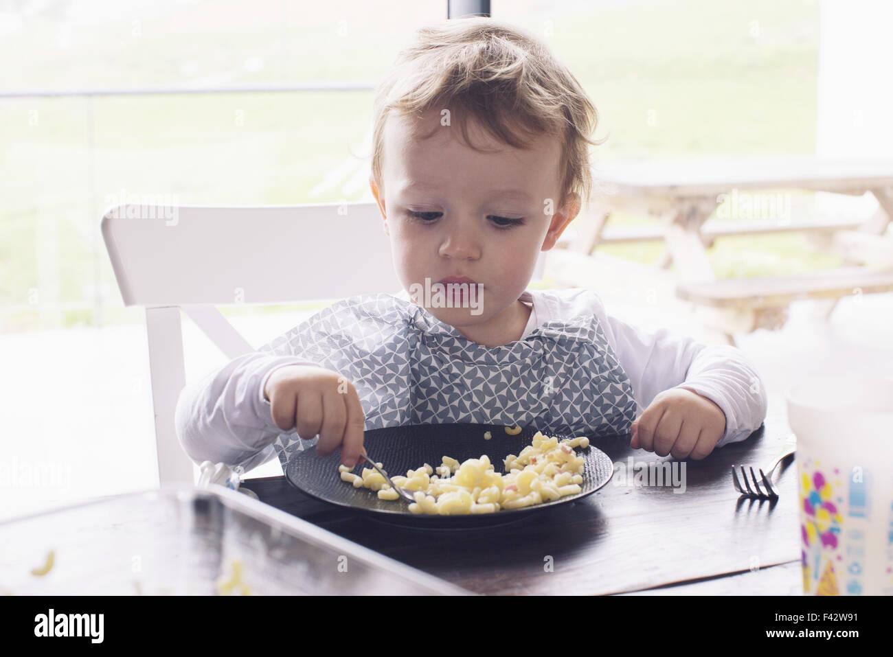 Little Boy eating macaroni Photo Stock
