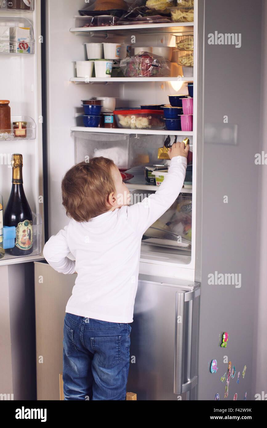 Petit garçon pour atteindre quelque chose dans le réfrigérateur Photo Stock