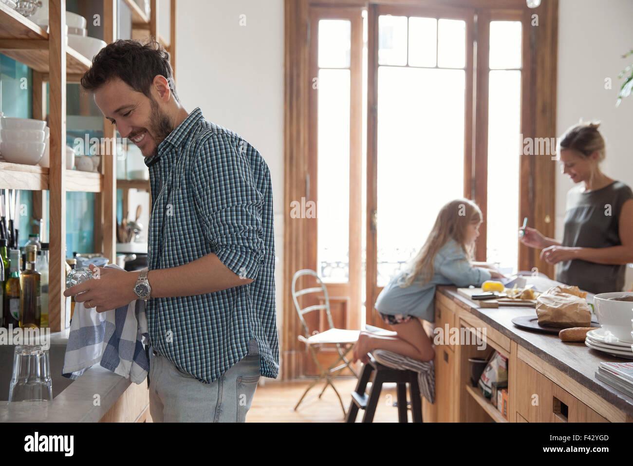 Dans la famille, l'homme cuisine vaisselle en premier plan Photo Stock