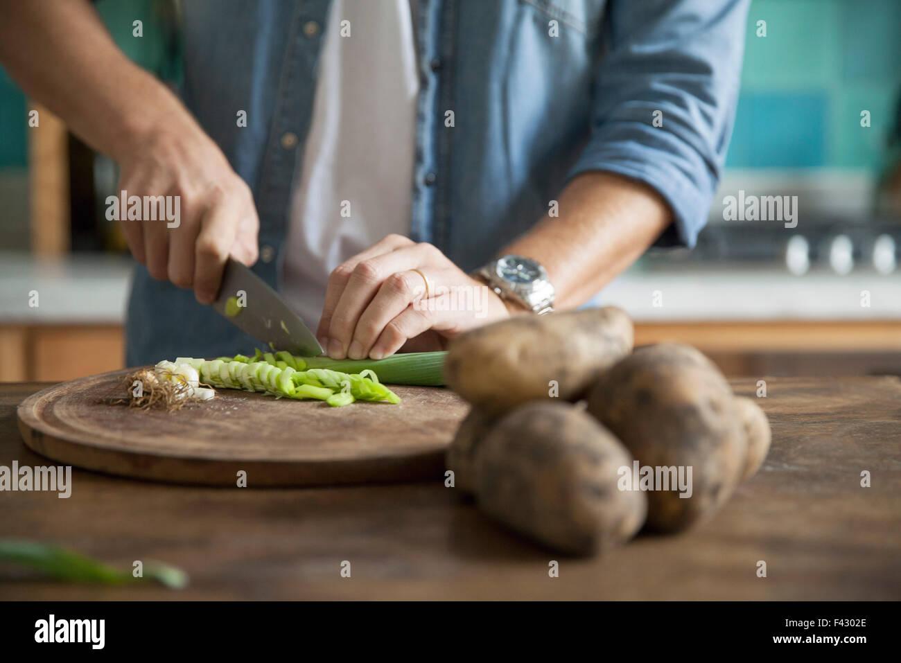 Coupe homme oignon de printemps dans la cuisine Photo Stock