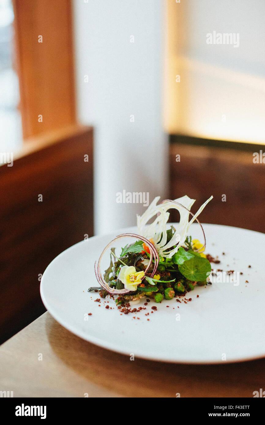 Près d'une assiette de nourriture élégamment présentées dans un restaurant de la ville. Photo Stock