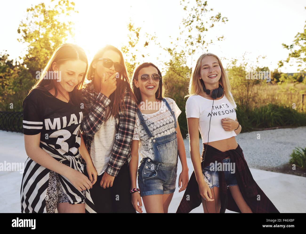 Quatre jeunes filles s'amusant dupant autour de l'appareil photo, de jour d'été Photo Stock