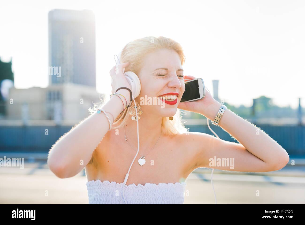 Demi-longueur portrait of young handsome young blonde long cheveux droits woman listening music avec des écouteurs Photo Stock