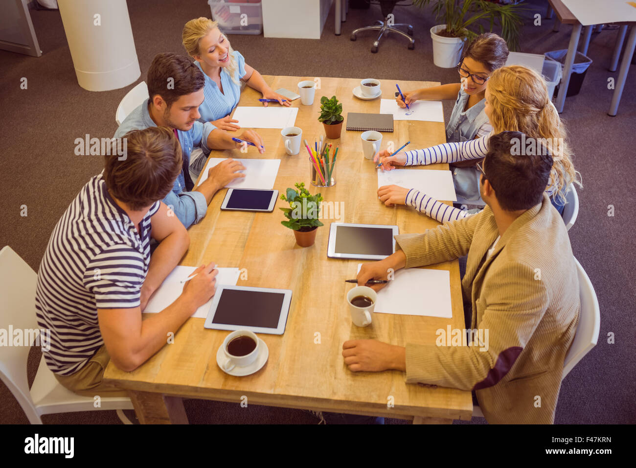 Collègues créatifs avec ordinateur portable et tablette numérique Photo Stock