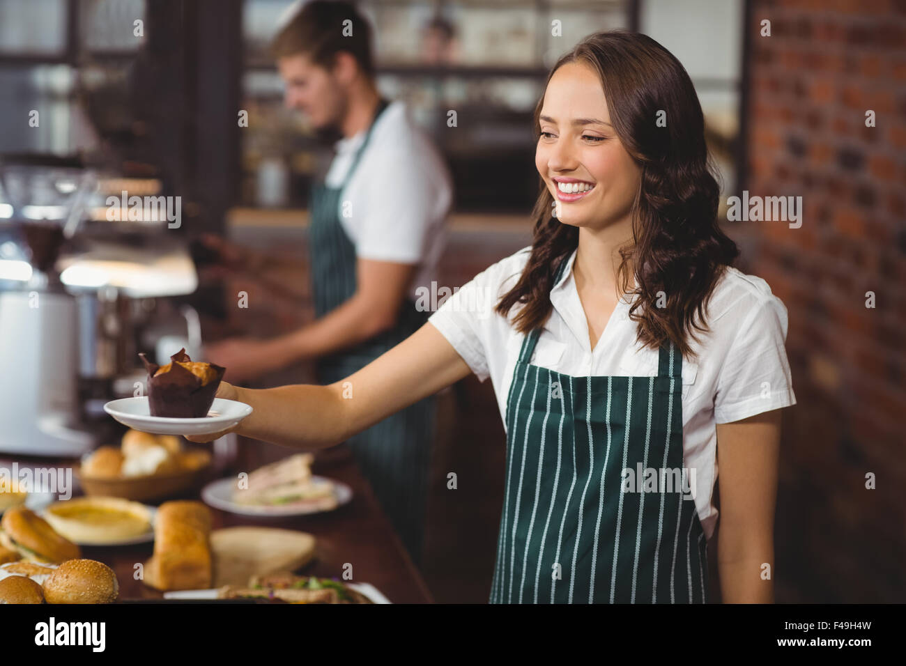 Smiling waitress serving un muffin Banque D'Images