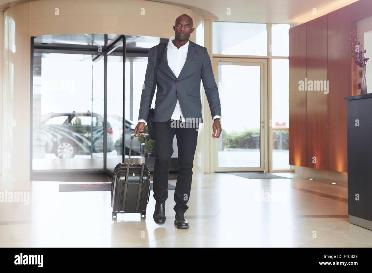 Businessman walking dans le lobby de l'hôtel. Portrait de jeunes cadres africains avec une valise. Photo Stock