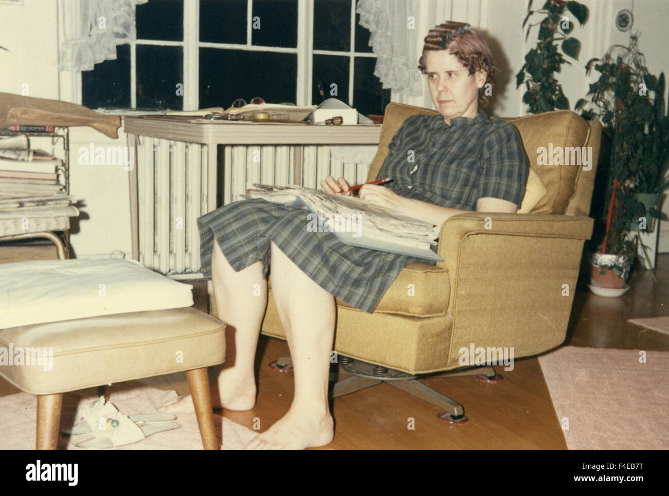 1960 femme fashion sitting in Chair in living room Photo Stock