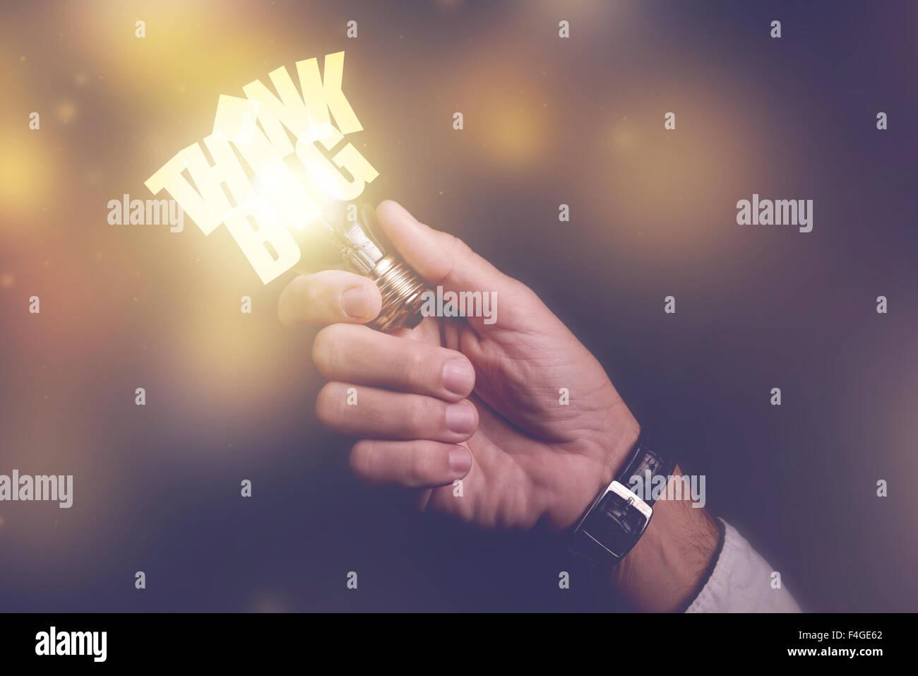 Pensez grand idées commerciales métaphore visuelle, homme d'affaires avec ampoule, image aux couleurs Photo Stock