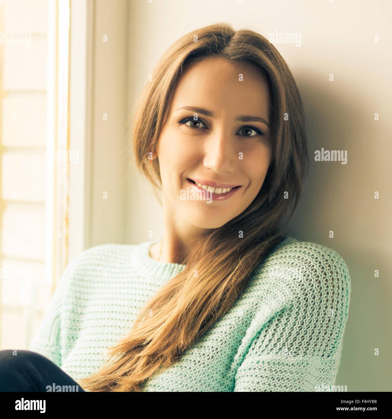 Young smiling woman détente sur l'appui de fenêtre. Les tons de couleurs chaudes de droit Photo Stock