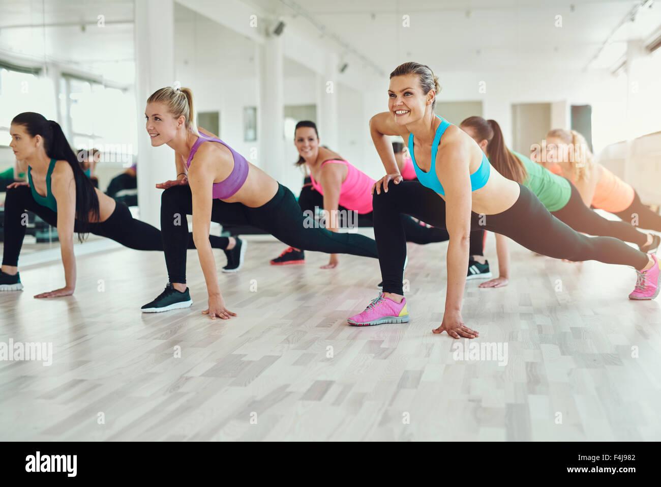 Fitness, sport, formation, sport et vie concept - group of smiling people l'exercice dans la salle de sport Photo Stock
