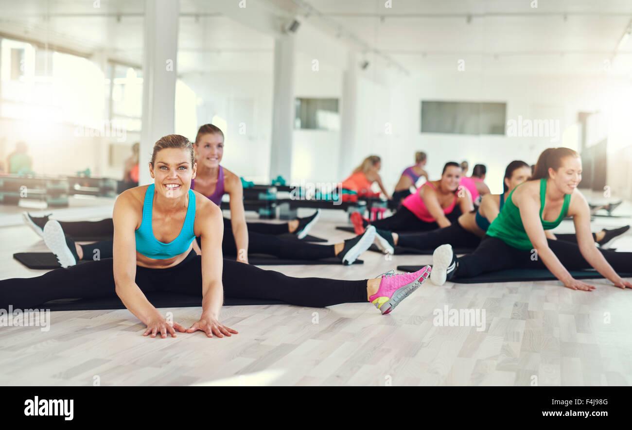 Groupe de femme aux étirements et exercices dans un cours de conditionnement physique, d'aérobic et Photo Stock