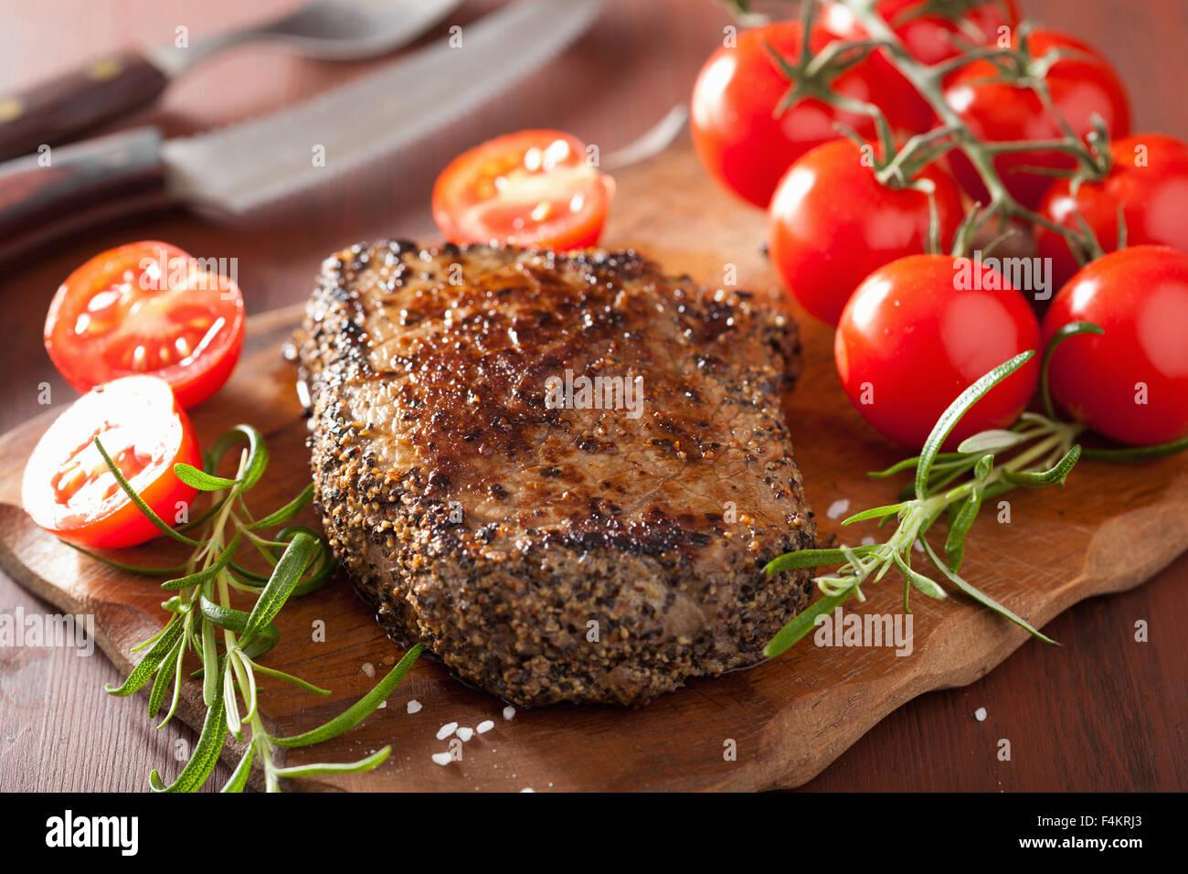 Pavé de boeuf aux épices et de romarin sur fond de bois Photo Stock