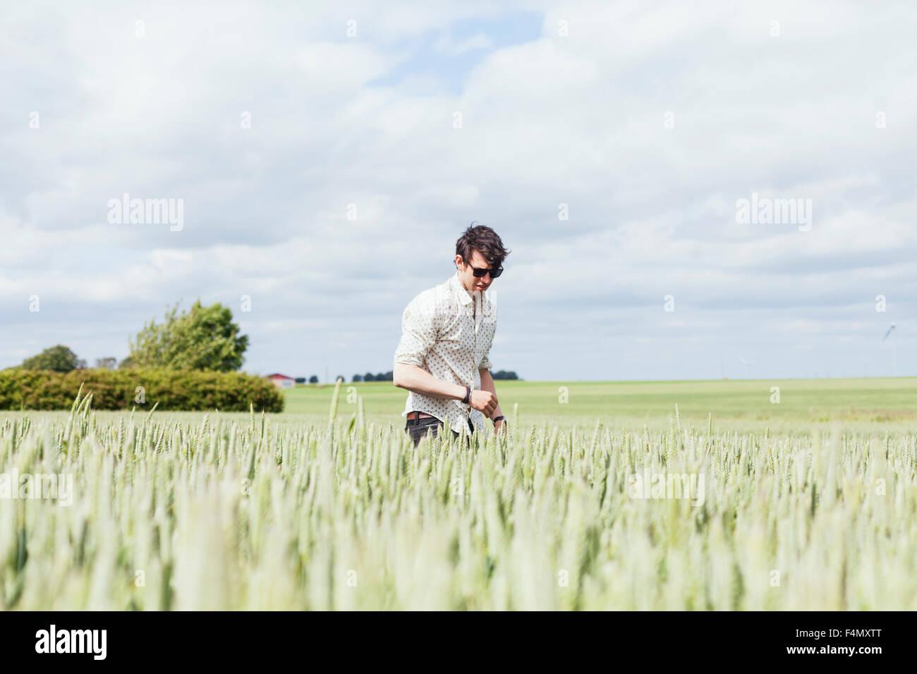 Jeune homme recherche sur field against cloudy sky Photo Stock
