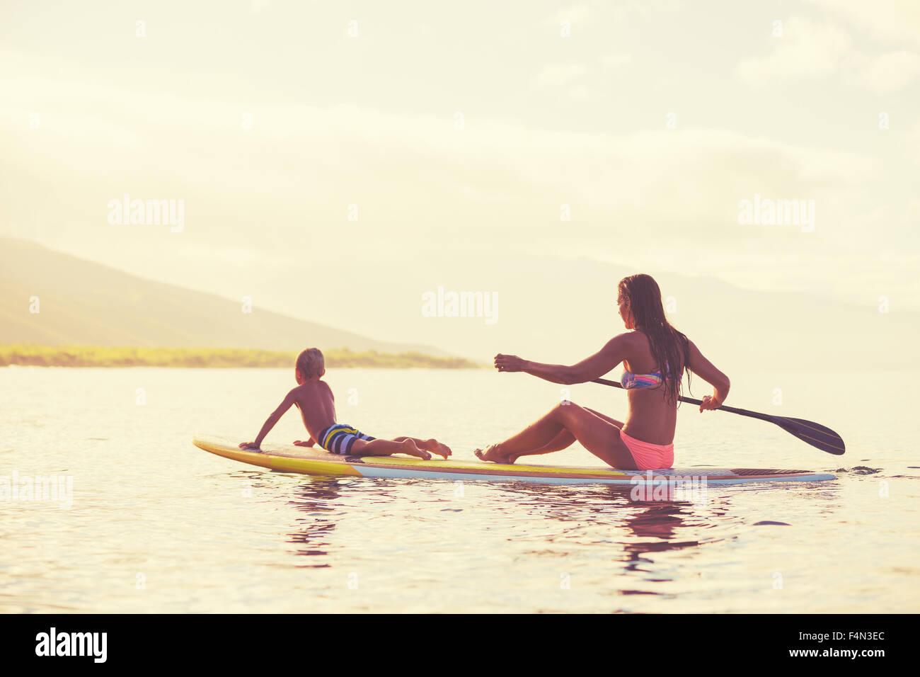 Mère et fils Stand up Paddling au lever du soleil d'été, de vie en plein air Photo Stock