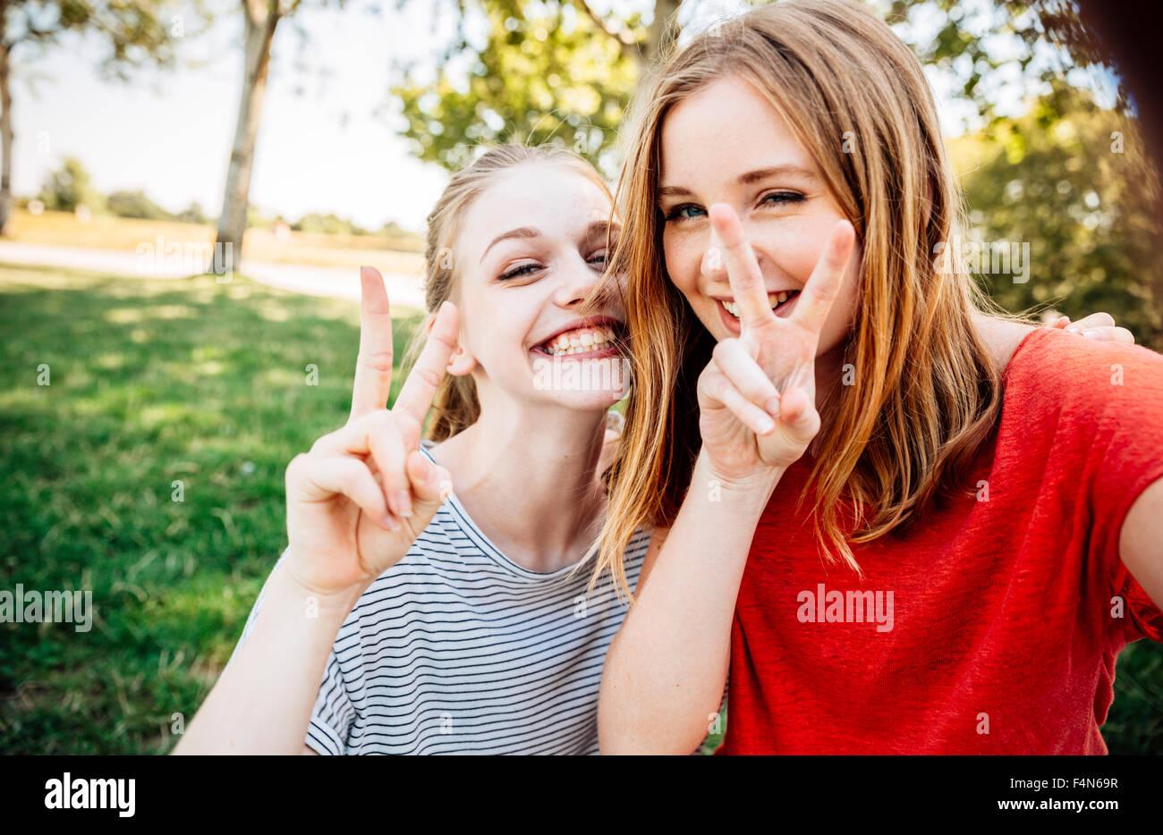 Deux adolescentes ludique faisant signe de victoire Photo Stock