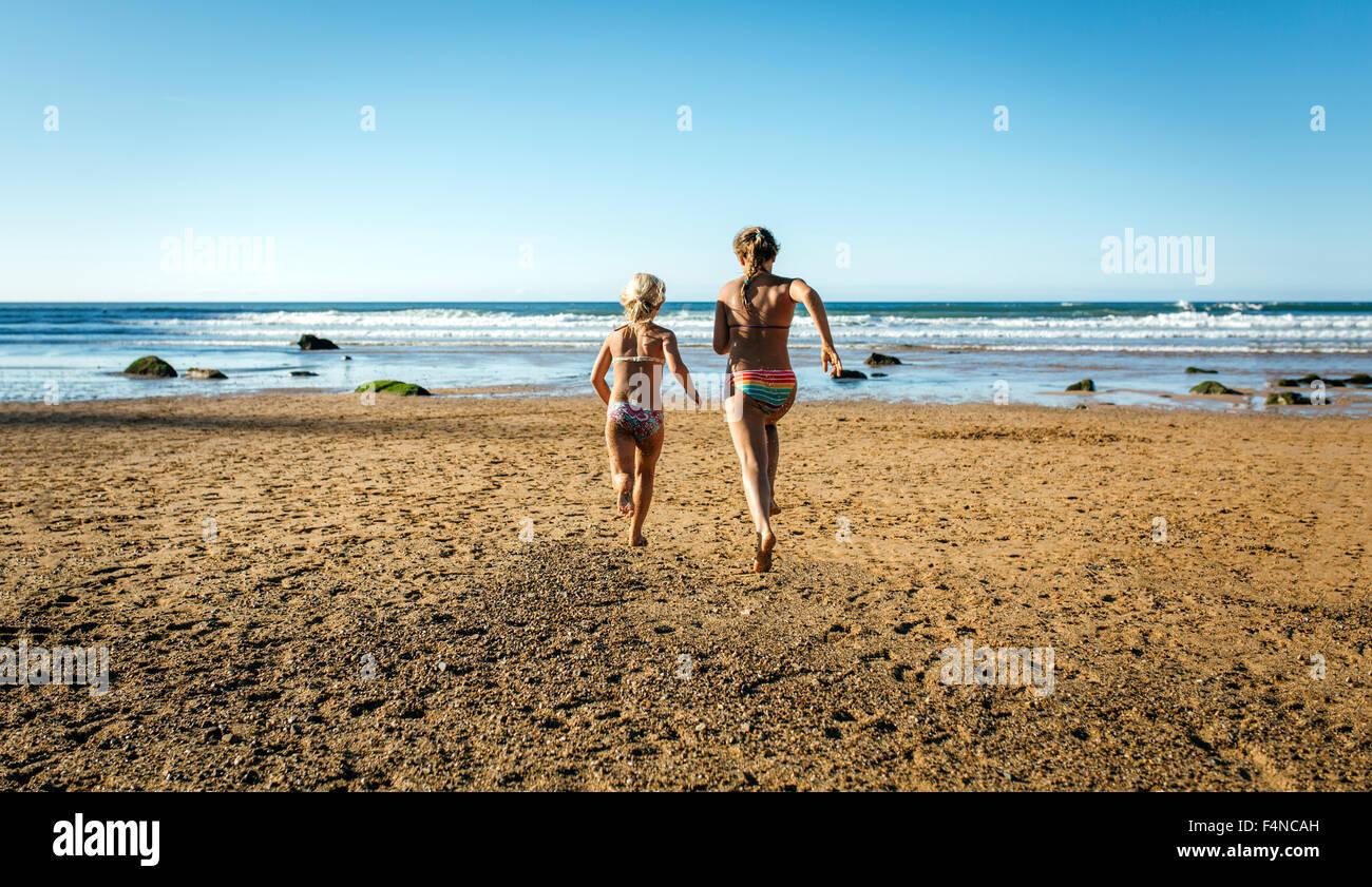Vue arrière des deux soeurs s'exécutant sur la plage Photo Stock