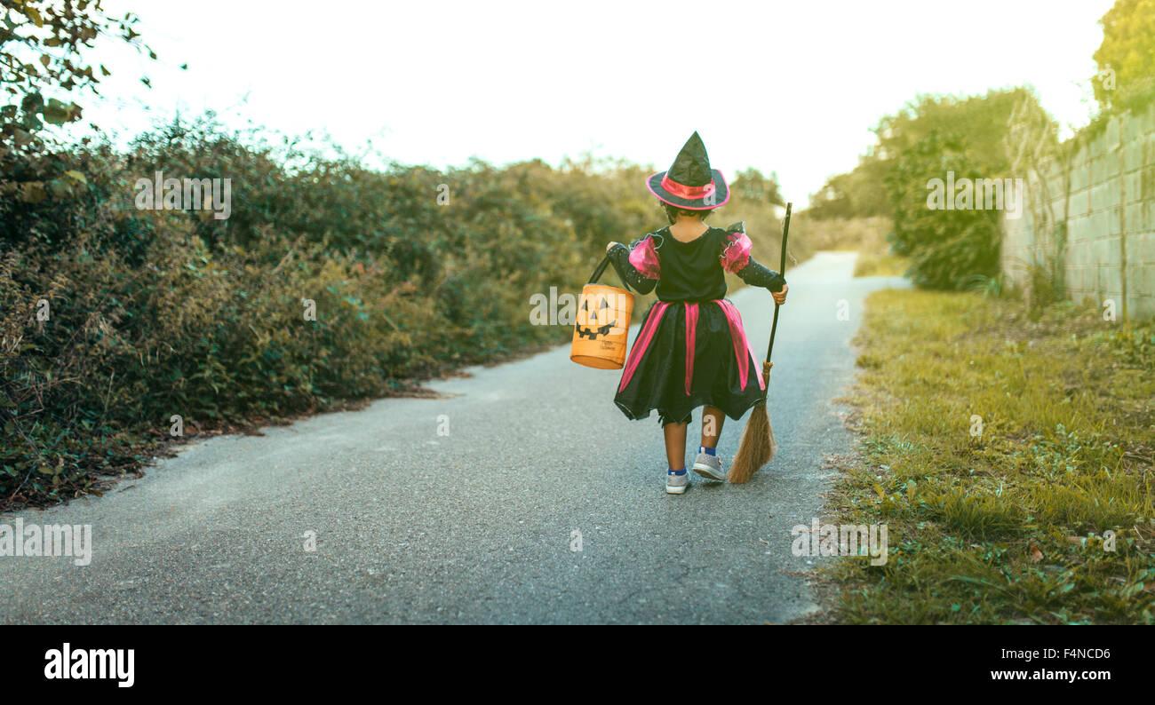 Vue de l'arrière petite fille de se faire passer pour une sorcière avec balai et lanterne d'halloween Photo Stock