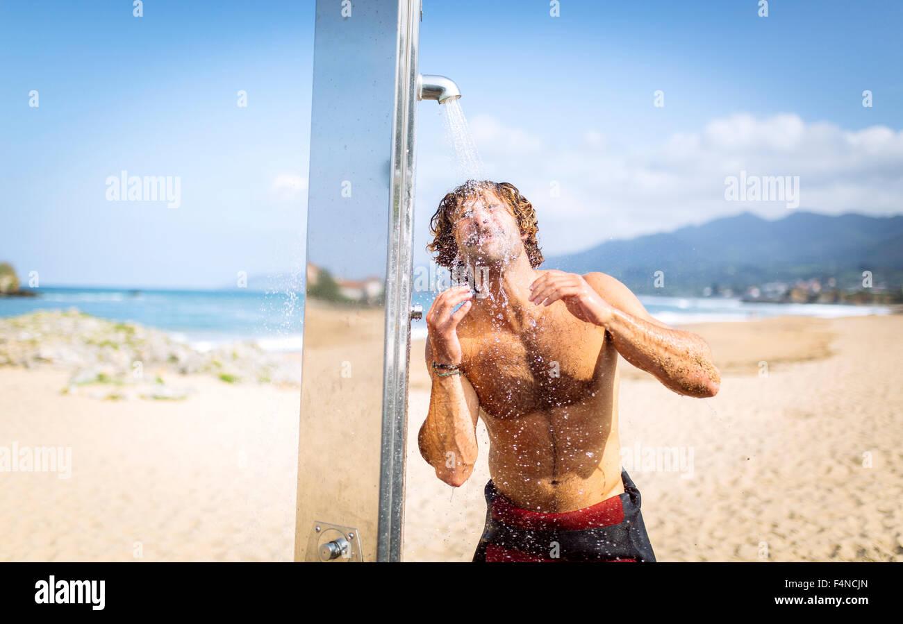 L'Espagne, les Asturies, Colunga, jeune homme sur la plage, sous la douche Photo Stock