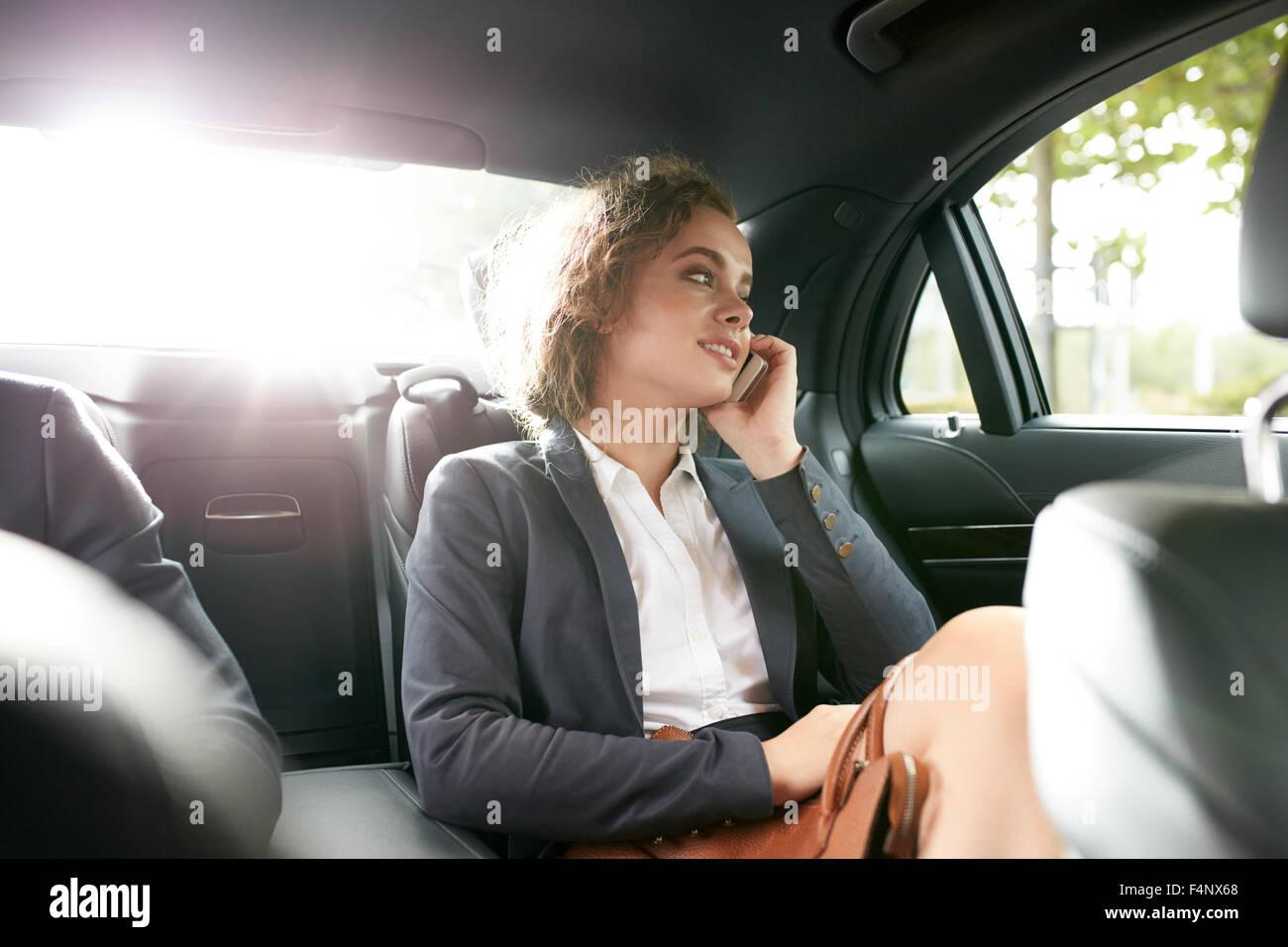Shot of young businesswoman pour se rendre au travail et dans la voiture de luxe sur le siège arrière Photo Stock