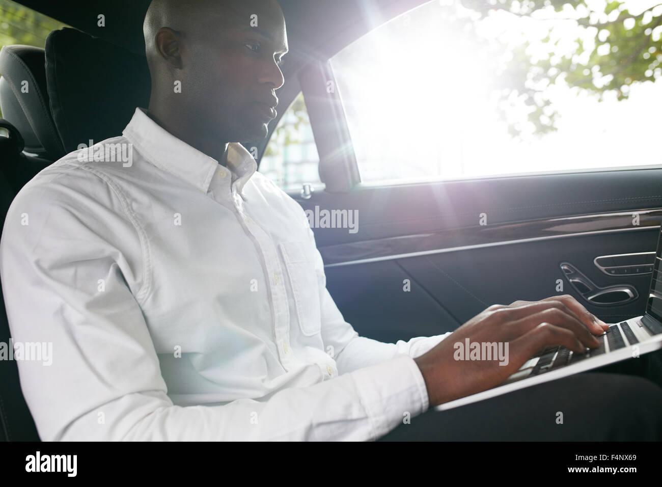 Homme d'affaires voyageant à bureau dans la voiture de luxe sur le siège arrière et de travail Photo Stock