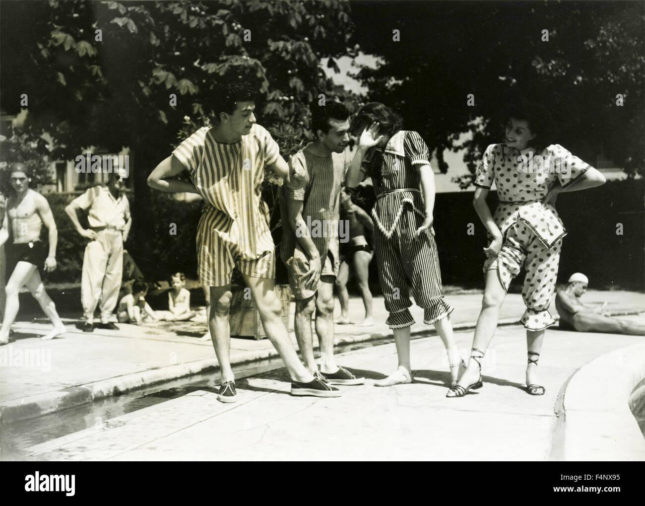 Deux paires de jeunes avec un drôle de vêtements sur la banque d'une piscine Photo Stock