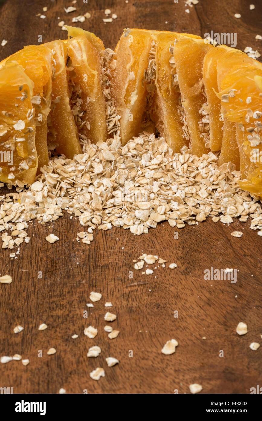 Orange a ouvert et l'avoine avoine ou sur une planche de bois. Gruau + orange = synergie alimentaire Photo Stock