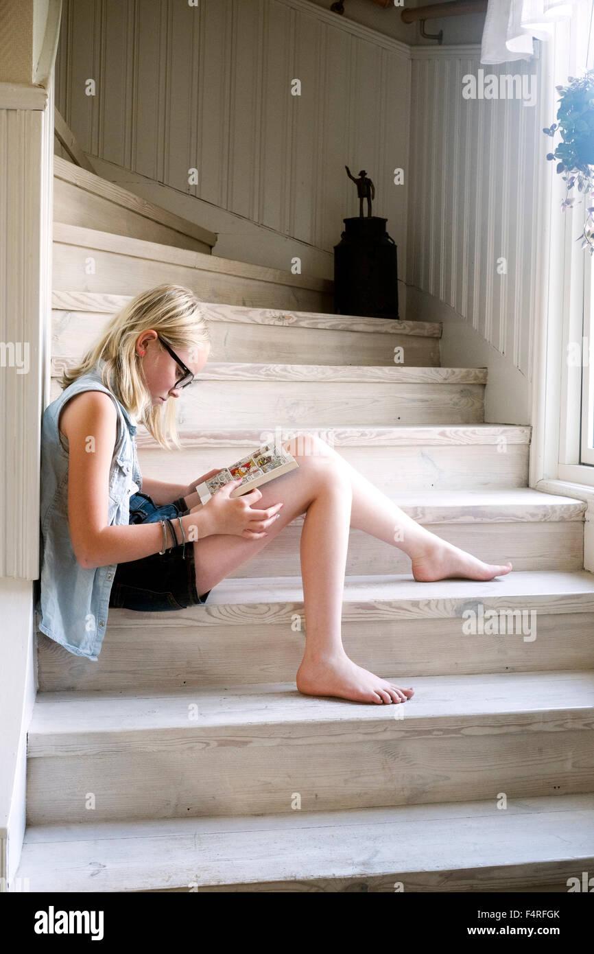 La Suède, Skane, Vejbystrand, Girl (10-11) La lecture de livre sur des marches de bois à la maison Photo Stock