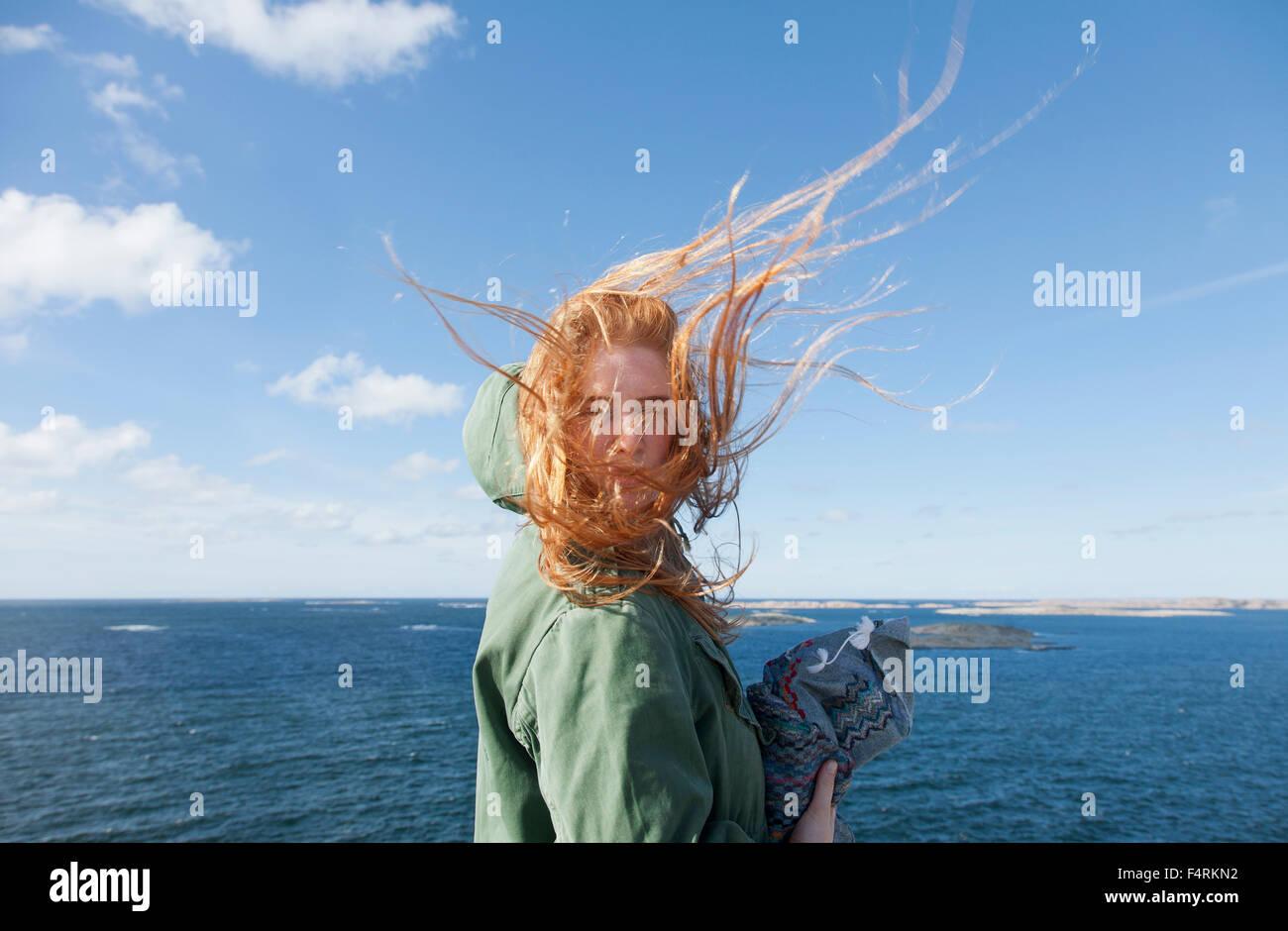 La Suède, la Côte Ouest Suédoise, Bohuslan, Skaftolandet, Jeune femme debout au bord de mer Banque D'Images