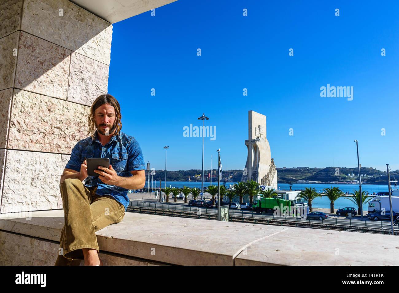 L'homme se lit d'une tablette électronique en face de l'icône portugaise, Monument des Découvertes Photo Stock